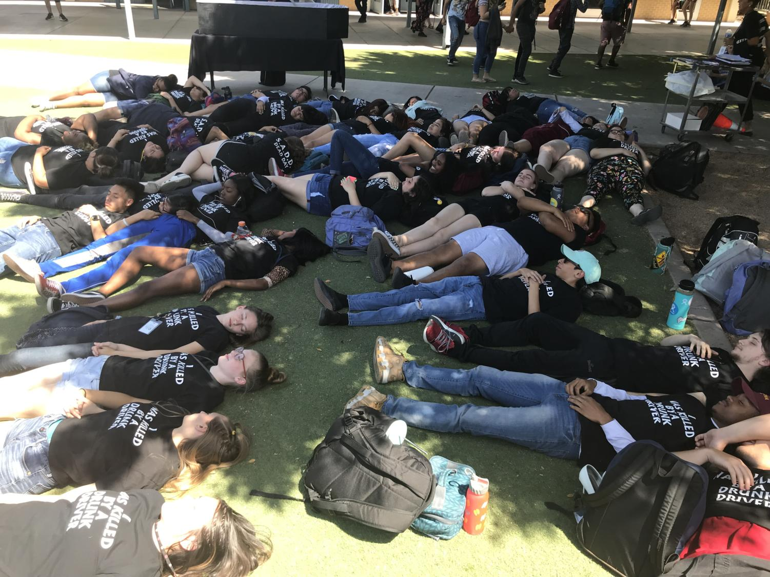 Students lay out on Senior Lawn donning shirts that say